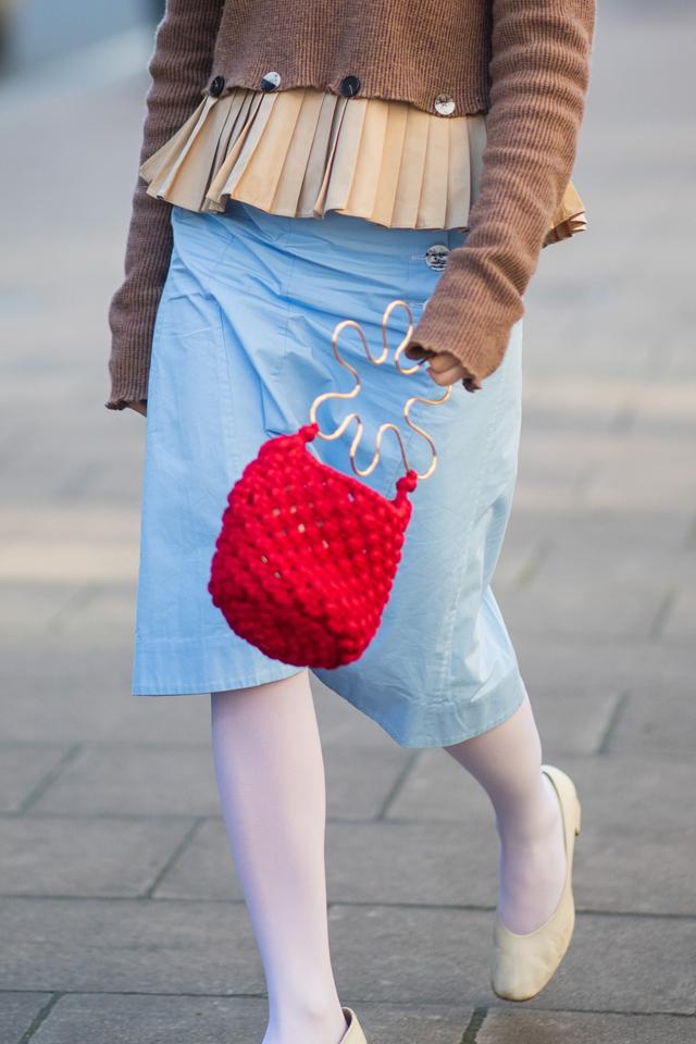 お花のようなユニークなハンドルデザインに、ハンドメイドのようなニット素材のバッグは個性的。バッグを主役にしたシンプルなコーディネイトもおしゃれだし、個性がさく裂したヴィンテージルックにもハマる。
