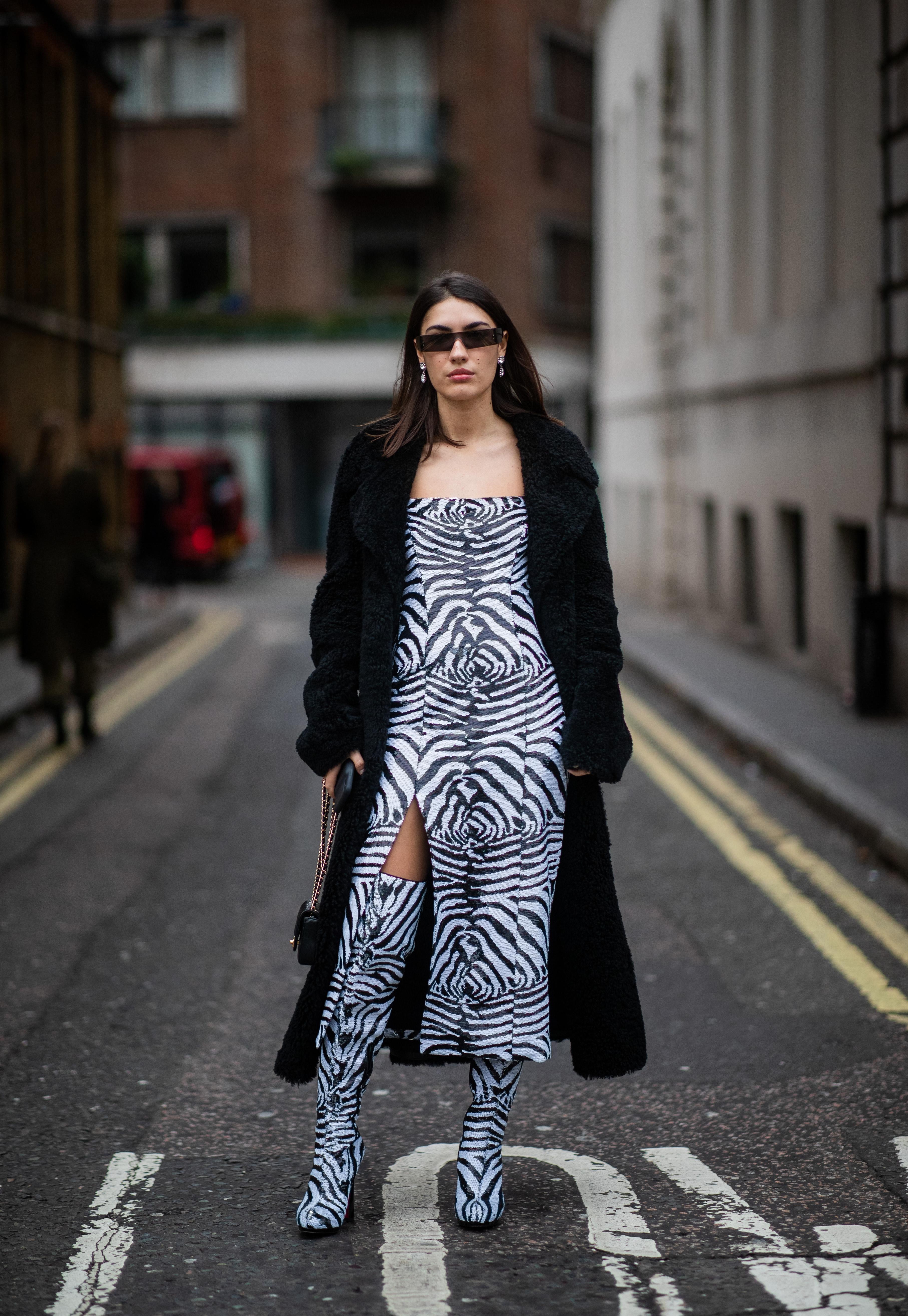 大胆なスリット入りのゼブラ柄ドレスに、セイム柄のロングブーツのコーディネイトはインパクト抜群! その他はブラックでまとめてモードなエッセンスも忘れずに。サイバーチックなスクエアのサングラスも効果的。