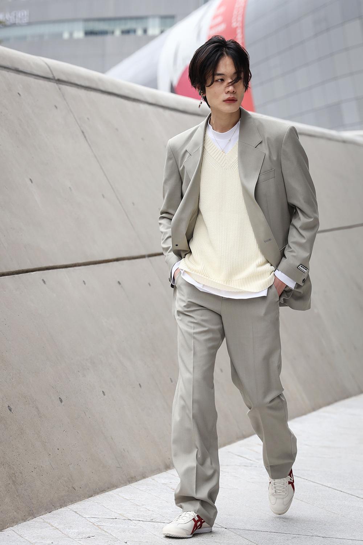 渋いカラートーンのスーツスタイルはカラーレスなコーディネイトが断然おしゃれ。トップスをレイヤードして、足もとにはスニーカーをイン! カジュアルな味付けで今っぽい空気感を纏って。