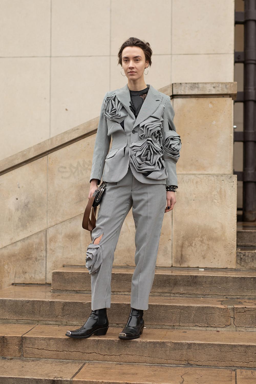 立体的なフラワーデザインが目を引くスーツは、それだけで雰囲気があるスタイルが完成する。小物はベーシックなデザインを選びつつも、スーツを引き立てるモードな重厚感を意識して。