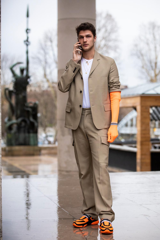 ワーク感あるベージュのスーツはシンプルにコーディネイトしつつも、オレンジアイテムをアクセントとしてイン。片手だけに取り入れたグローブはまるで皮膚の一部のようなフィット感があっておもしろい。