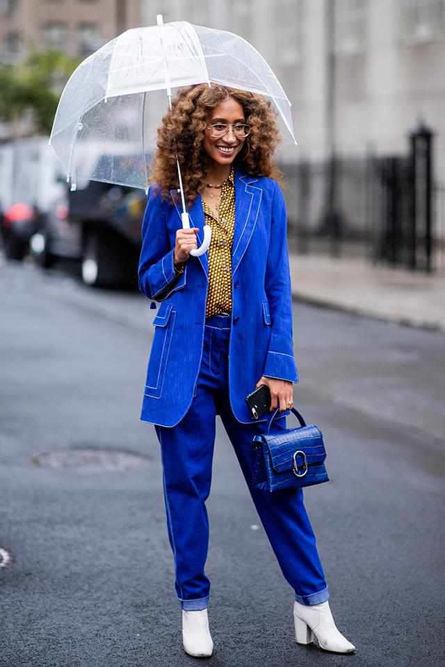 スーツのようなきちんと感のあるコーディネイトは、デニムの上品な一面を見せてくれる。ボリューム感あるヘアスタイルや、メタルフレームのメガネがオリジナリティを演出している。