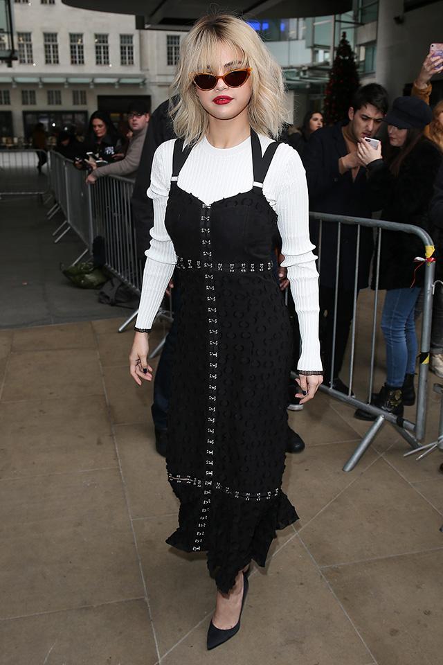 大胆なヘアチェンジが話題になったセレーナ・ゴメスは、そのブロンドカラーによく似合う、ブラックドレスをシンプルにスタイリング。シャープなレンズデザインのサングラスが効いている。