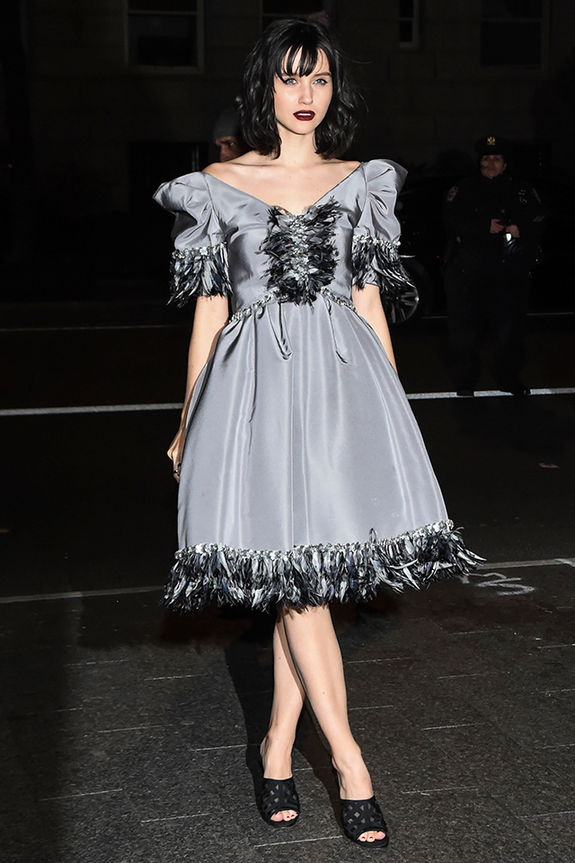 フェザー使いが特徴的なグレーカラーのドレスは、ゴシック調のヘアメイクと相まってダークネスな雰囲気に。周りと一線を画したスタイルが完成。ノーアクセでドレスの存在感を際立たせて。