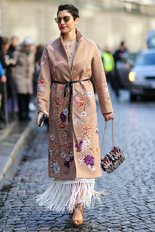 全体的に描かれた花柄のコートをワンピース風にスタイリング。フリンジアイテムとのレイヤードが技あり! ウェアが引き立つように、アクセサリーは最小限に。ベリーショートのヘアスタイルも雰囲気あり。