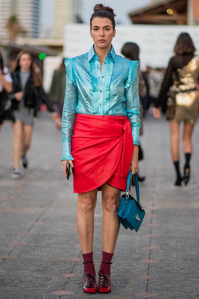 鮮やかなブルーブラウス×レッドカラーの巻きスカートのスタイリングがおしゃれ。フロントや肩、袖などにフリルがあしらわれたモードなブラウスだから、カラーコーデも品よくまとまる。