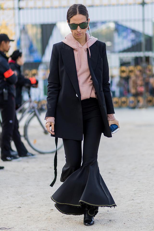 ブラックコーデにインしたサーモンピンクのフーディが可愛い! フリルのようなベルボトムパンツが、トレンド感のあるモードスタイルに昇華。プレーンなスタイルながら、こだわりをトッピングしたスタイリングは真似したい。