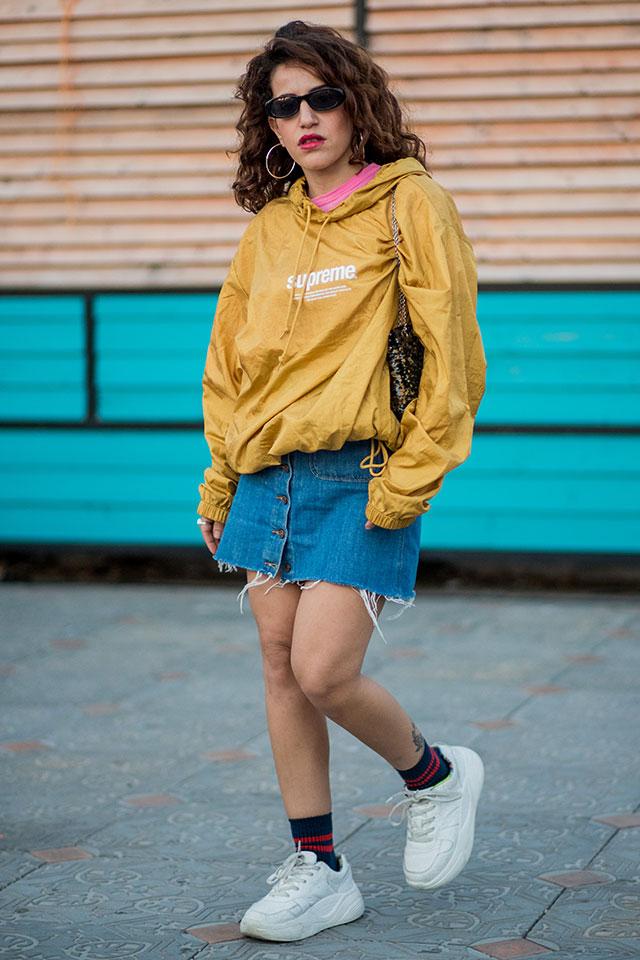シャカシャカ素材のブルゾンは、切りっぱなしのデニムスカートと合わせて90'sカジュアルを楽しんで。フープ―ピアスも雰囲気を盛り上げる。チラッと見えるピンクカラーのインナーが効いている。
