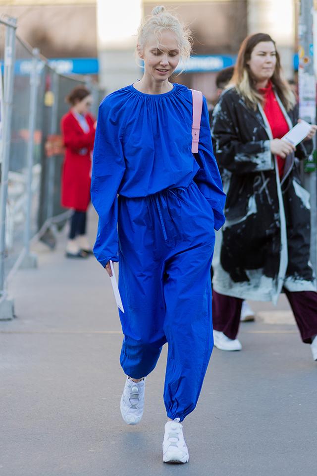 鮮やかなブルーが目を引くジャンプスーツはそのカラーのインパクトを活かして、ノーアクセでまとめるのがおしゃれ。ホワイトスニーカーやラフにまとめたヘアスタイルも今の気分にマッチする。