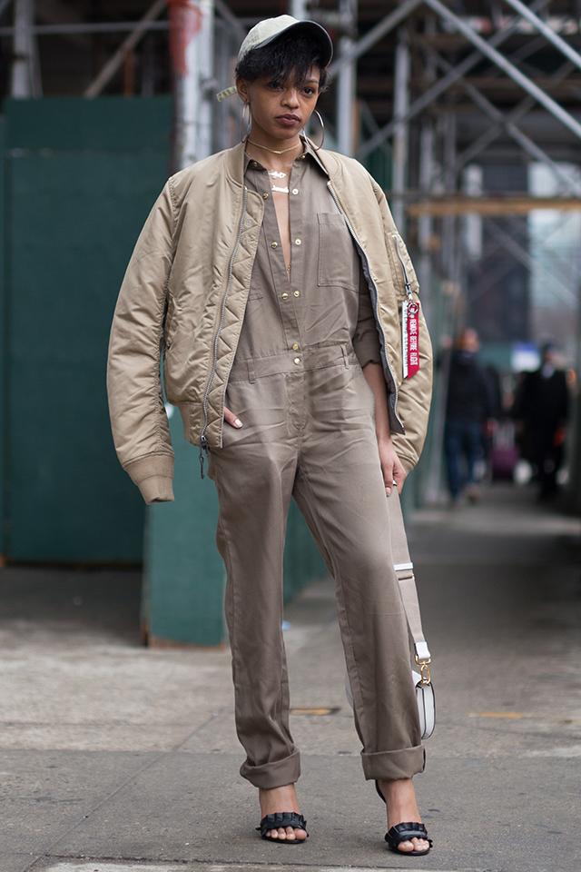 アースカラーでまとめたコーディネートが目を引くジャンプスーツスタイルは、大胆に開けたボタンや華奢なシューズを取り入れたスタイリングでフェミニンさをプラス。ストリートとのミックス感も◎。