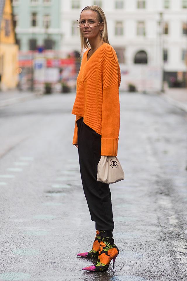 色鮮やかなオレンジカラーが目を引くニットは、ブラックパンツと合わせてクールさをトッピング。ルーズなシルエットでキメすぎないリラックス感がおしゃれ度をアップ。ブーツにもオレンジを取り入れたスタイリングがナイス!