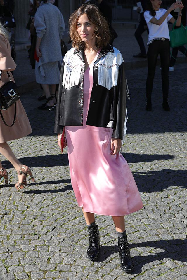 アレクサ・チャンはガーリーな印象の光沢感あるピンクのワンピースをハードなレザージャケットでテイストをミックス。フリンジデザインと、バイカラーのデザインがクールな雰囲気を演出してくれる。足元のワークブーツでおしゃれを格上げ!