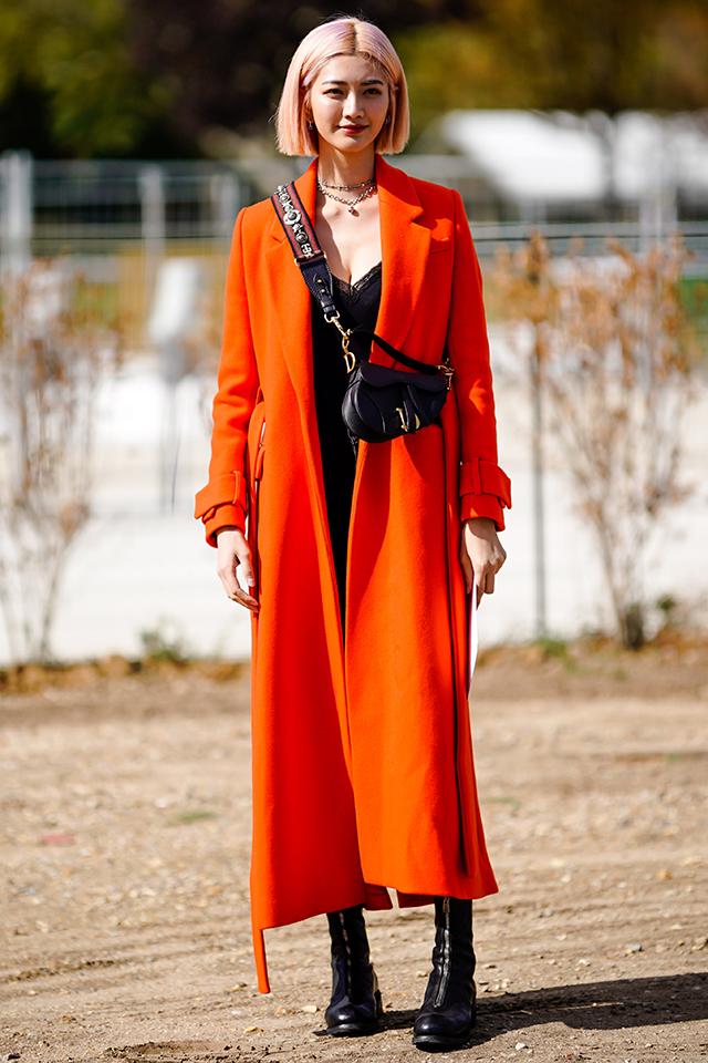鮮やかなオレンジカラーは、インパクトがある分モードなスタイリングを意識。そのほかをブラックアイテムでまとめたことで洗練された雰囲気に。ハイトーンカラーのヘアスタイルもおしゃれ。