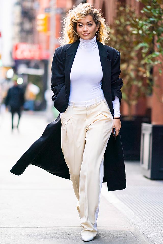 リタ・オラのミニマルなパンツルックがかっこいい! トーン違いのホワイトコーデに、ネイビーのロングアウターをオン。コーディネイトに馴染むアクセサリー使いもお手本にしたい。