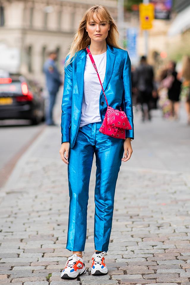光沢感あるブルーのスーツルックは、マニッシュな雰囲気を楽しみたい。足元にはトレンド感あるスニーカーを取り入れつつ、反対色のバッグでスタイルに変化をつけて。ナチュラルなヘアスタイルが抜け感になって◎。