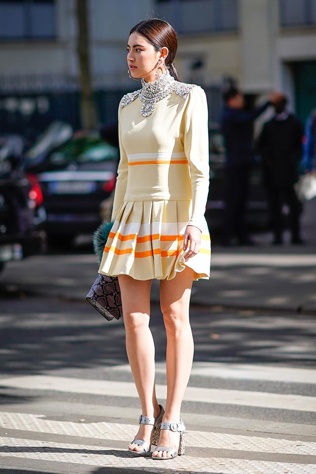 ベージュイエローにオレンジのボーダーでどこかスポーティなワンピースは、ネックレスのようなデコラティブなデザインでドレスとしても活躍する。ワンピースが引き立つよう、小物はベーシックカラーでコーディネイト。