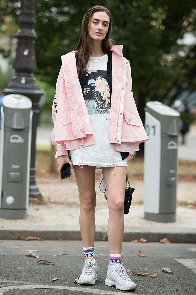 カジュアルなナイロン素材のアウターは、カラーリングで印象に変化を出して。ワンピースのように着こなしたTシャツと少しずつ丈感を変えたレイヤードスタイルはセンスあり! ソックス×スニーカーの組み合わせも◎。