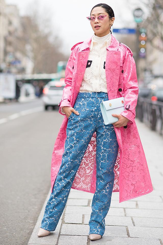 トレンドのPVC素材のレース柄トレンチでピンクを取り入れた春の装い。同じくレース柄のシャツやパンツでコーディネイトしたスタイリングは上級者ルック。スタイリングに馴染みつつも個性的な小物が効果的。