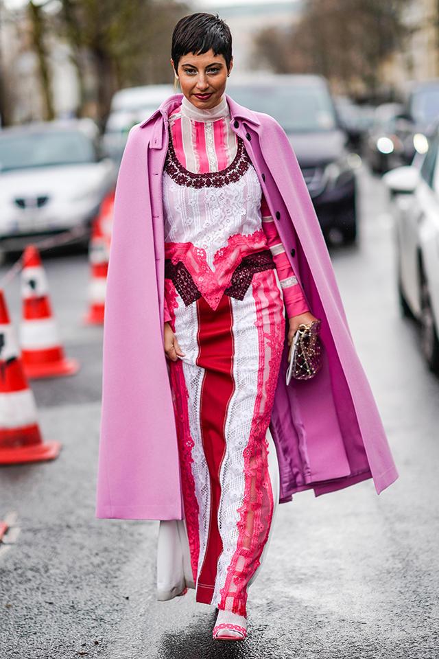 レーシーなドレススタイルの仕上げにマントをオン! いろんなピンクがある中でも、パープルピンクは、女性らしい雰囲気と、モードな着こなしを叶えてくれる。ミニマルなヘアスタイルもおしゃれ。
