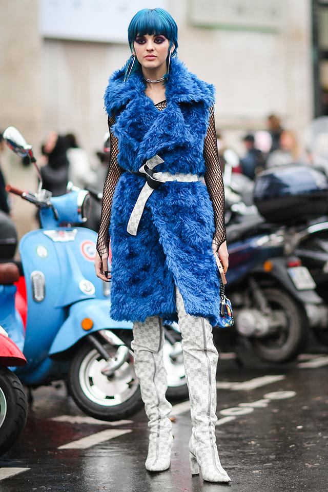 ワンピースのように着こなしたゴージャスなカラーファーのベストコートとメッシュトップスのレイヤードが新鮮! ブルーカラーのヘアスタイルとも相まって、ストリートで目立つこと間違いなし。