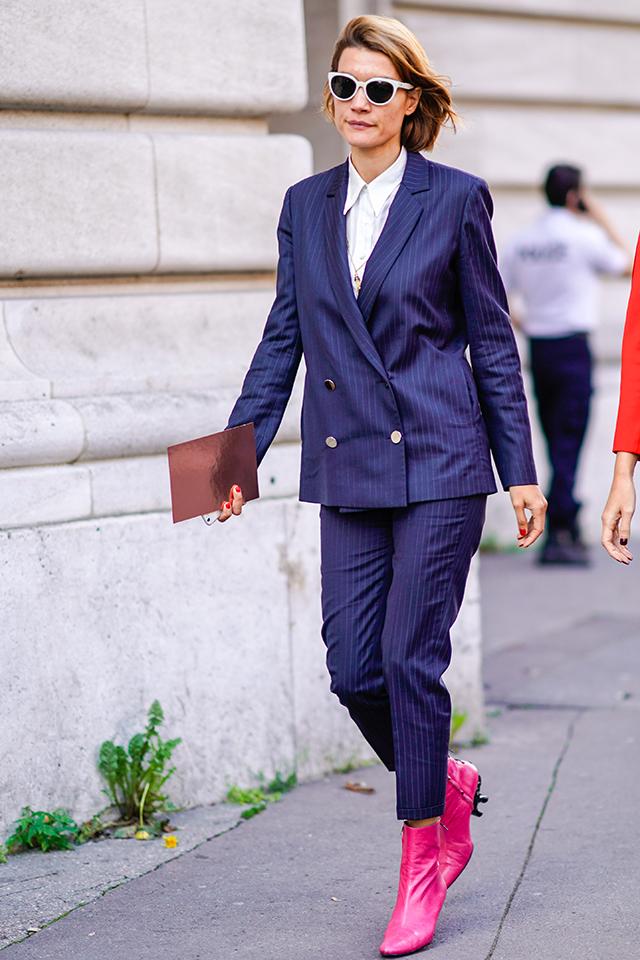 ダブルボタンのパンツルックは、キャリアウーマンな印象。シャツをきちんと着こなして、上品さを保ちつつ、ピンクのショートブーツで遊びを見せたスタイリングがおしゃれ。ホワイトフレームのサングラスも◎。