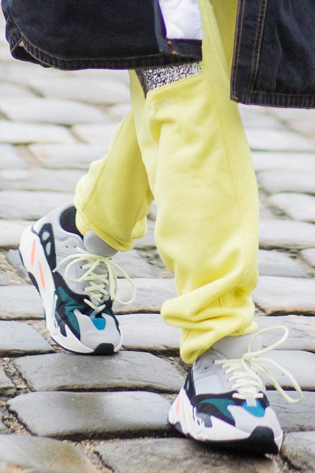 膝まであるオバーシルエットのアウターに、ラフなネオンエロ―のスウェットパンツと、ストリートな雰囲気がおしゃれ。足元はもちろんスニーカーで! スポーツカジュアルなスタイルを楽しんで。
