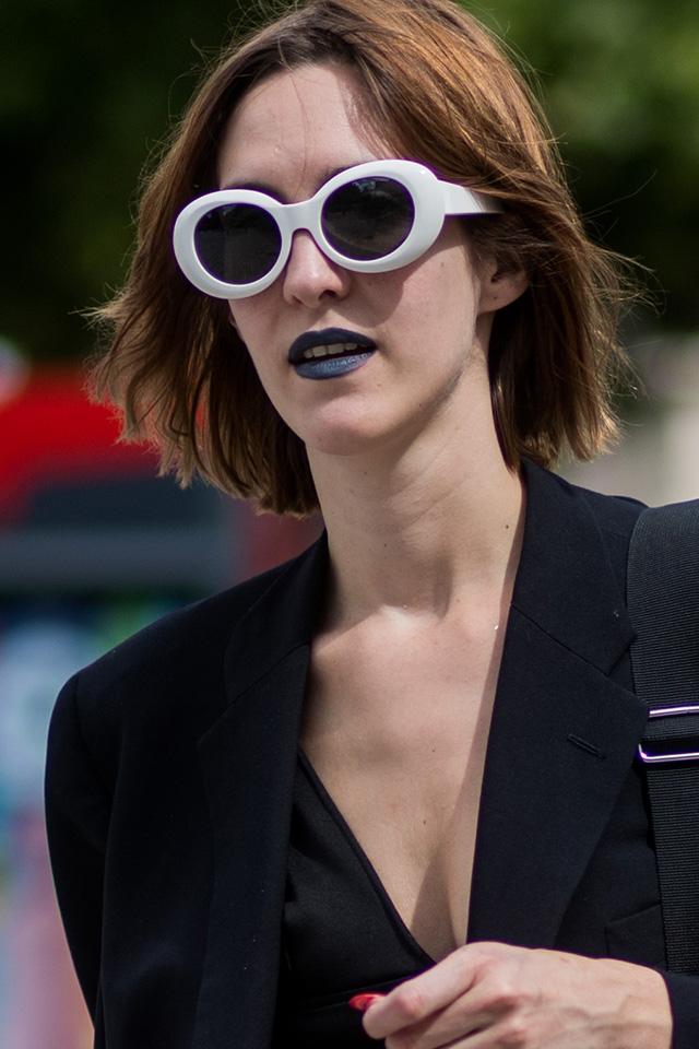 存在感抜群のホワイトフレームのサングラスは、コーディネイトのアクセントとして活躍。オールブラックスタイルの差し色として取り入れて。ダークカラーなリップも雰囲気を盛り上げてくれる。