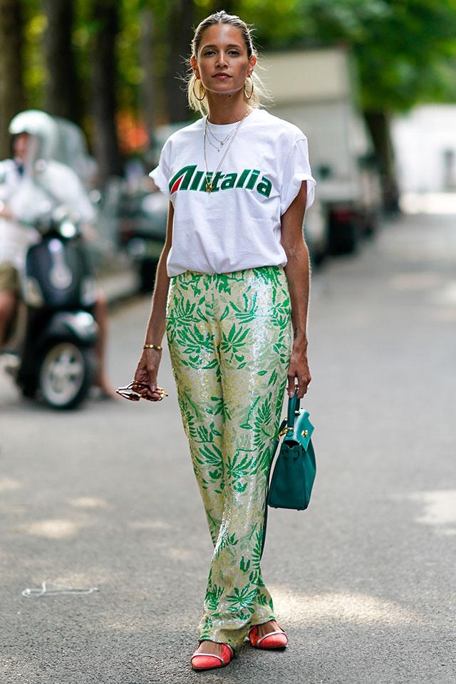 ラフなシルエットにグリーンのロゴが映えるTシャツは、リラックスパンツとスタイリング。光沢感ある素材だから、抜け感がありながらもモードな雰囲気をまとえる。カラー小物を投入!