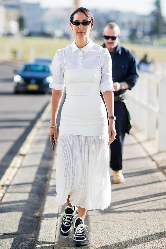 ガーリーな印象のプリーツスカートは、コルセットのようなボディコンシャスワンピースを重ねてモード仕立てに。足元はハイテクスニーカーで決まり! シャープなヘアスタイルもおしゃれさを後押しする。