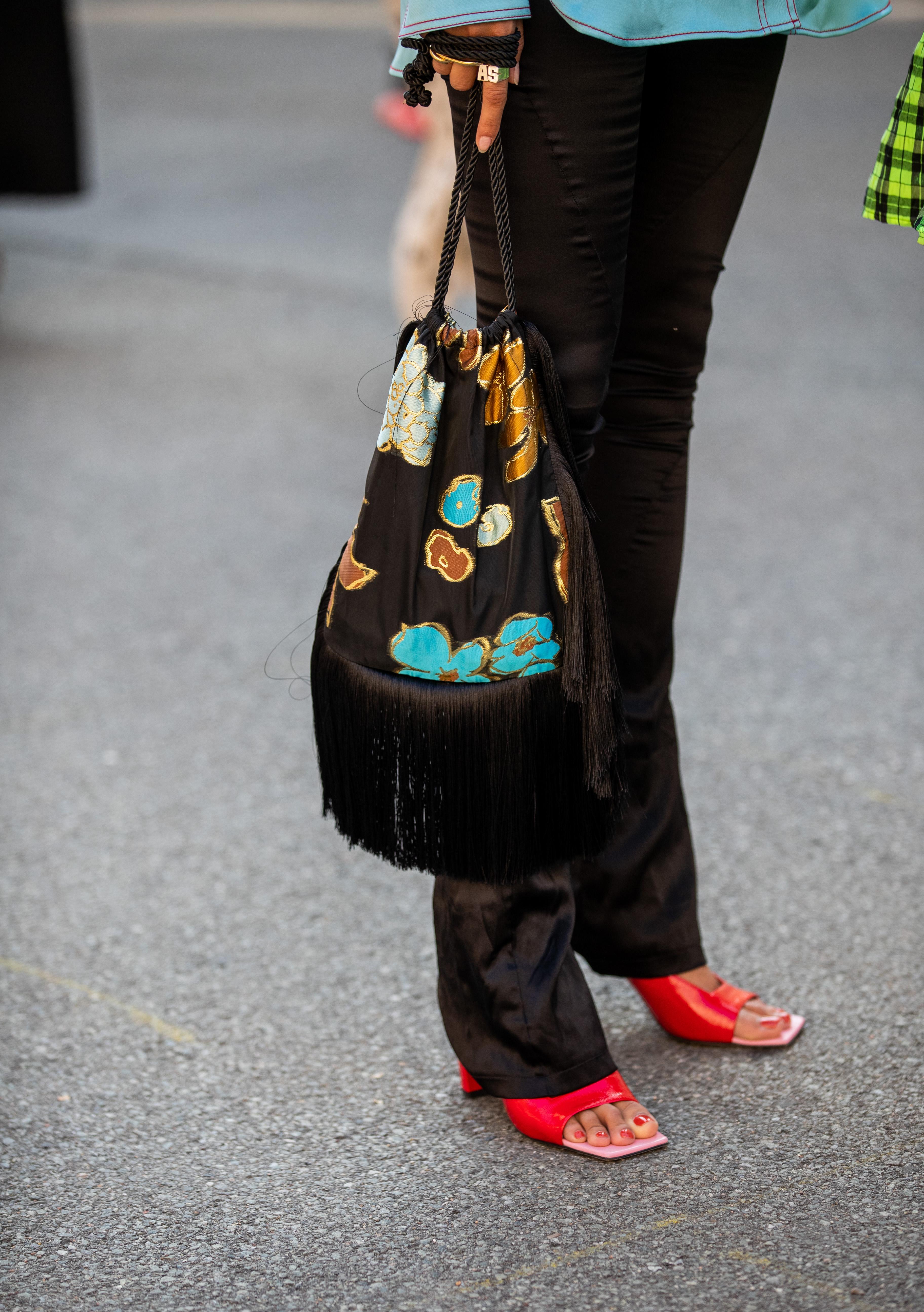 ブラックパンツにはパキッと映えるレッドカラーのサンダルをインして足元の存在感を高めつつ、女性らしさが加わることでより印象的に仕上がる。セイムカラーのペディキュアを可愛い。