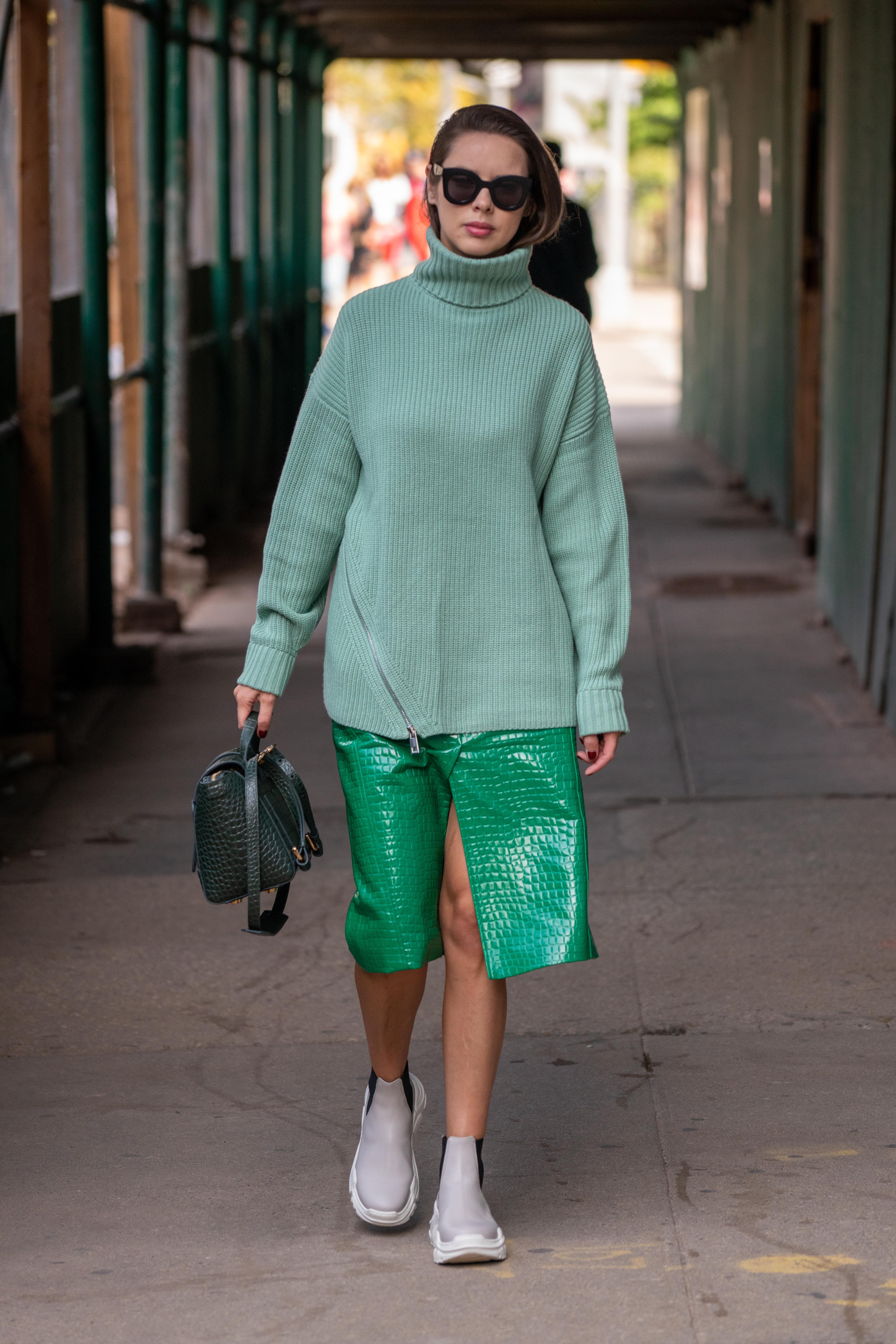 大胆なフロントスリップ、エコレザーの質感など、モードな雰囲気のミディスカートは、ざっくりニットでカジュアルダウンさせて。ストリートさトレンド感を高める。足元はスカートとの丈感がGOODなショート丈スニーカーを。