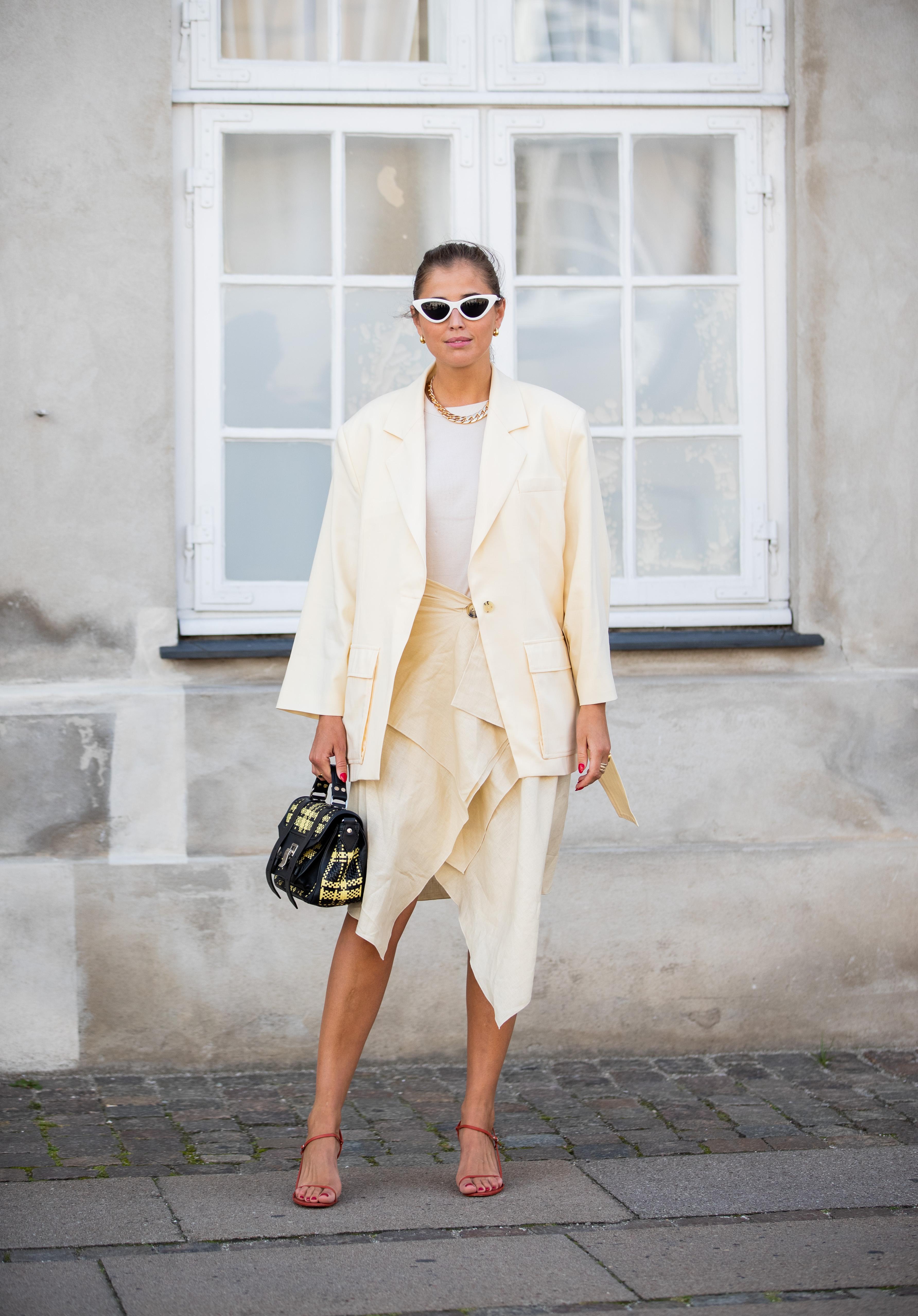 アシンメトリーなデザインがクールなスカートはジャケットと合わせてセットアップのようなスタイリングに。オフホワイトのカラーニュアンスがレディさを作り出す。華奢なサンダルも雰囲気にフィット。