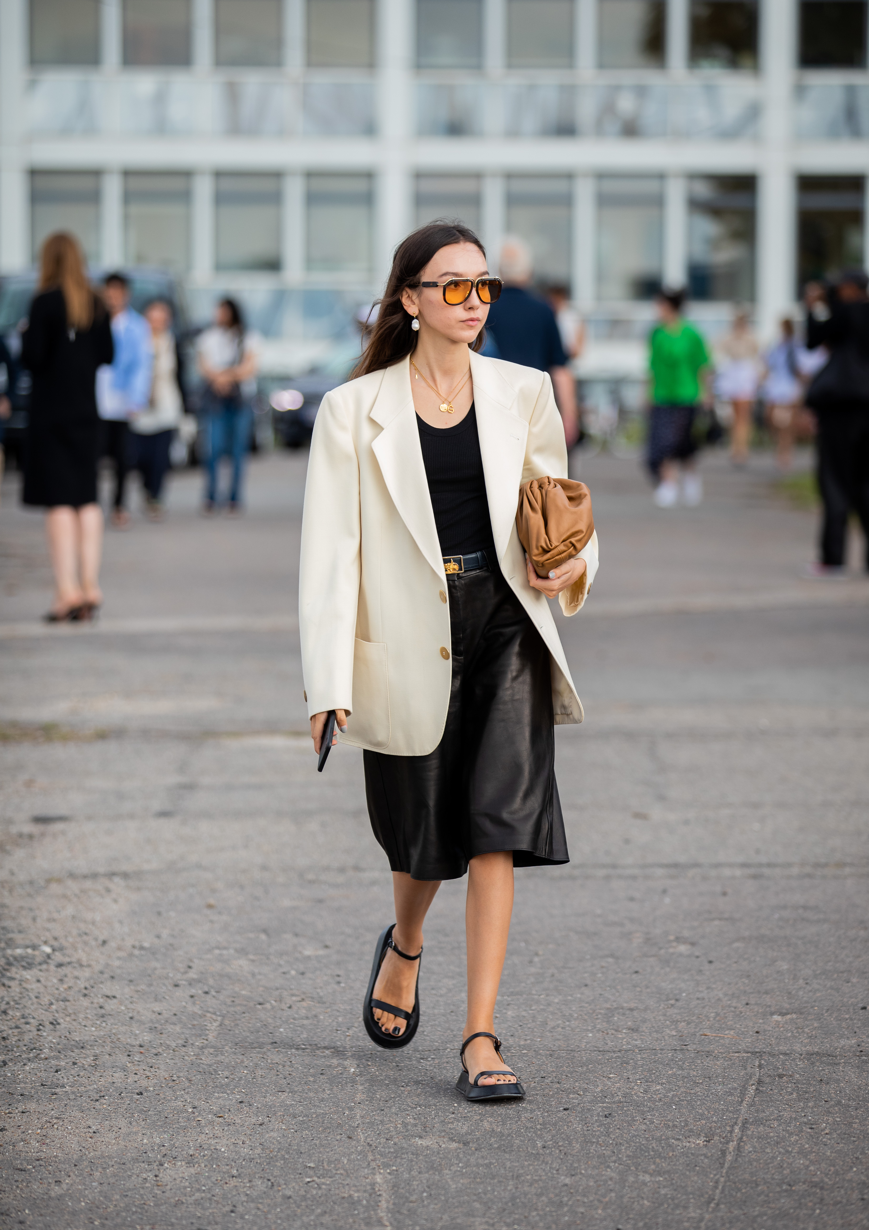 レザー調のミディ丈スカートはモード指数高め。ビッグシルエットのジャケットとコーディネイトしたモノトーンルックはクール。足元にはスポーティなサンダルをインして抜け感を演出。