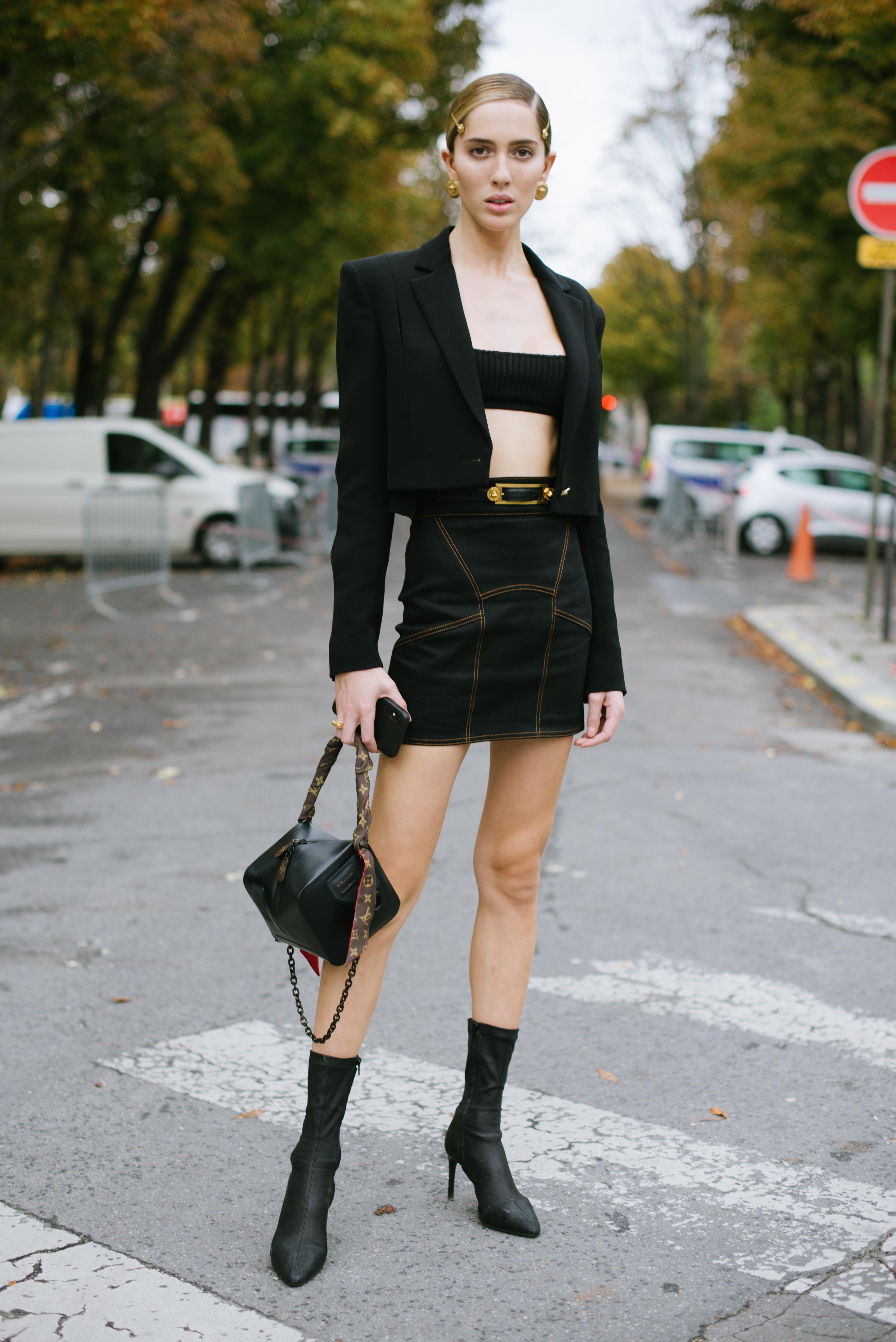 オールブラックにゴールドのアクセントがモードな雰囲気を演出する。タイトミニのスカートはステッチデザインですっきりした印象。肌露出があるからこそ、堂々とした着こなしを披露して。
